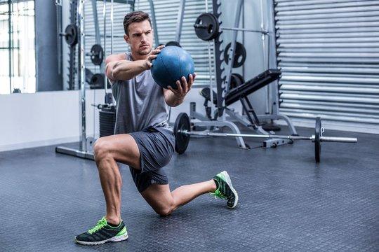 Muscular man doing medecine ball exercises