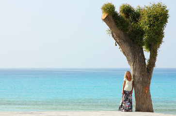 girl standing near a tree on the beach