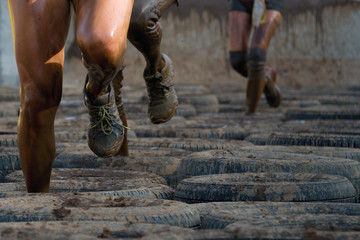 Mud race runners, tries to make it through the tire trap Wall mural