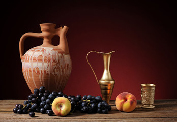 Ceramic pitcher and fresh grapes on table