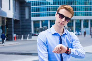 Portrait of young businessman looking at the clock and waiting for the client