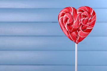 Bright lollipop in shape of heart on wooden background