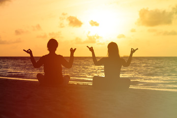silhouette of couple doing yoga at sunset