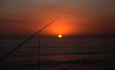 Silhouette Fishing Pole at sunset on the ocean