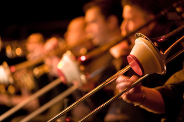 Trombone section with cup mutes. Shallow focus on the foreground trombonist with the rest of the section falling into background blur.  Big band brass section with cup mutes.