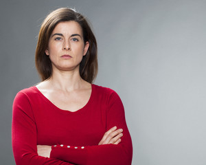 serious young woman with brown hair and red sweater staring with arms crossed for reinsurance and protection
