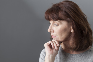 thinking mature woman with brown hair and grey sweater on profile,looking serene or with SAD syndrome,copy space