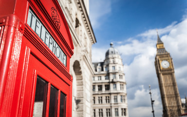 London phone box. Detail of an iconic red British telephone box with Big Ben visible in the background.