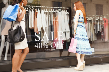 Two shoppers looking into the window of a store with a sale sign.