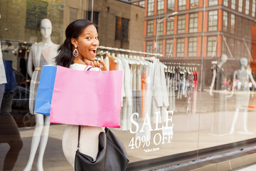 A happy young woman with shopping bags over her shoulder smiling at the viewer..