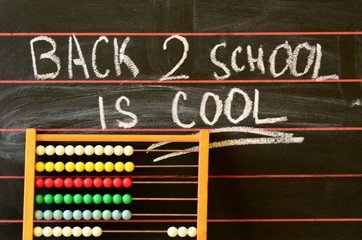 Back to school written on blackboard and abacus.