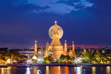 Wat Arun Temple in night with the moon at bangkok thailand.