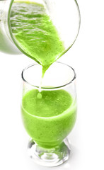 Pouring green healthy juice in glass isolated on white