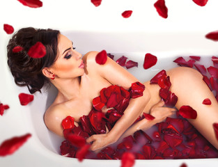 Sexy beautiful naked brunette woman laying in a bath with milk and red romantic rose petals looking at camera. Luxury spa and skin care