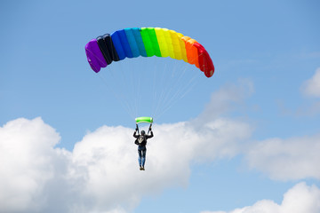 Parachutist on a bright  parachute  rainbow colors on bakcground blue sky with clouds