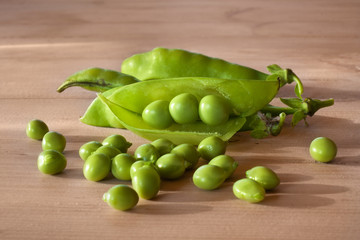 green pea pods on the wooden table