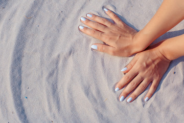 Female hands playing in white sand
