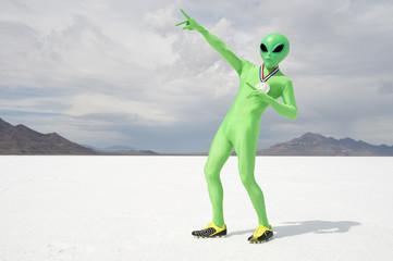 Green alien track star athlete wearing gold medal celebrating with lightning bolt pose on stark white planet background