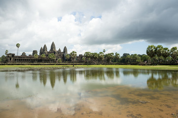 Ancient temple complex of Angkor Wat reflecting in still water under dramatic sky