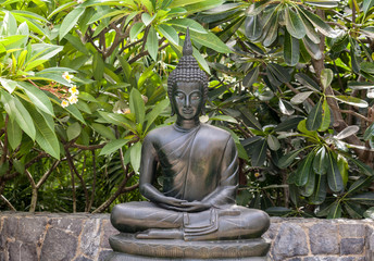 Metal buddha statue lotus pose in the garden.