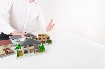 白いテーブルで一戸建てをプレゼンしている男性
