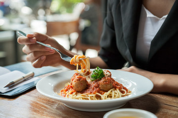 focus on woman eating spaghetti with journal