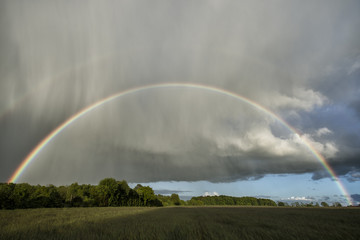 Double rainbow over a field with sunshine and rain