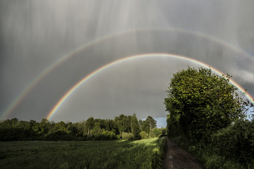 Spectacular double rainbow with sunshine and rain