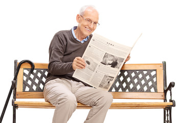 Senior reading a newspaper seated on a bench