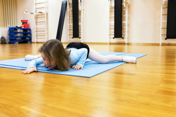 Child, a girl is engaged in ballet, gymnastics, yoga in the gym