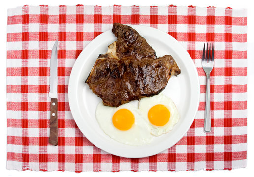 T-Bone Steak and Fried Eggs Breakfast – Two sunny side up eggs and a T-Bone steak on a white plate. Table setting, with fork and steak knife. Red checked background.