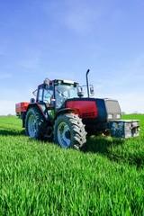 Landwirt auf einem Traktor bei der Düngung