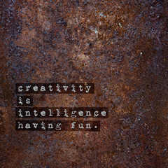 Motivational poster over rusty metal CREATIVITY IS INTELLIGENCE.