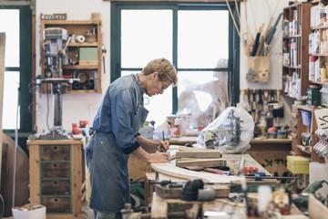 Senior woman artist drawing on wood in workshop