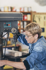 Senior woman artist using a drilling machine in workshop