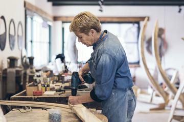 Elderly woman artist drilling wood in her workshop