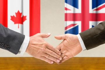 Vertreter Kanadas und Großbritanniens reichen sich die Hand