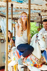 On a summer day a group of friends having fun in the shade on a carousel with horses and blowing soap bubbles. In the foreground a young woman in the air while blowing many colorful soap bubbles