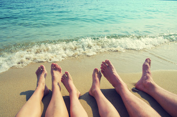 Female, children's and male feet on a beach against the sea in a summer sunny day. Family holiday