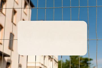 Unbeschriftetes weisses Schild an einem Bauzaun
