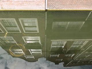 sich im Wasser spiegelnde Häuser an einer niederländischen Gracht, in der sich ein versenktes Fahrrad befindet
