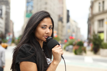 A female newscaster talking into her microphone.