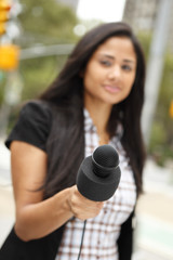Woman holding microphone as if interviewing the viewer. Focus is on microphone.