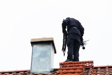 Kaminkehrer oder Schornsteinfeger kehrt Schornstein auf Haus
