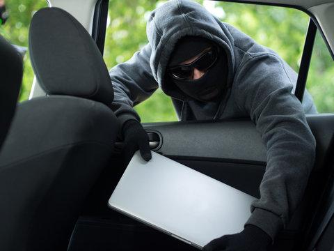 Car theft - a laptop being stolen through the window of an