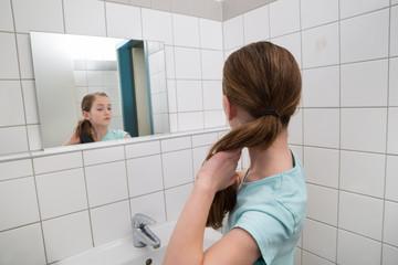 Girl Tying Hair In Bathroom