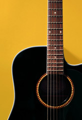 Detail of black acoustic guitar on yellow wall, with shadow