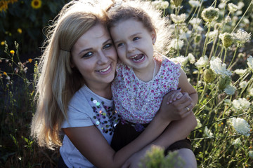 Mother and a daughter in the sunflowers