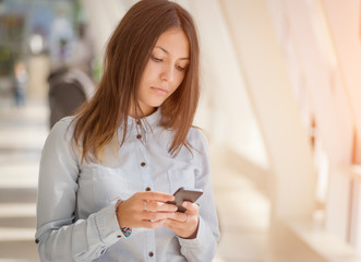 Young businesswoman inside office with smartphone.
