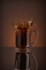 Ice cappuccino splash, refreshing mug of coffee on brown background.